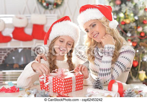 Retrato de feliz madre e hija con regalo de Navidad - csp62453242