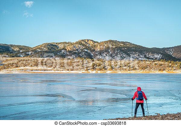 hiker at frozen mountain lake - csp33693818