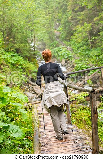 Hiker with hiking poles looking walking over wooden bridge in a forest - csp21790936