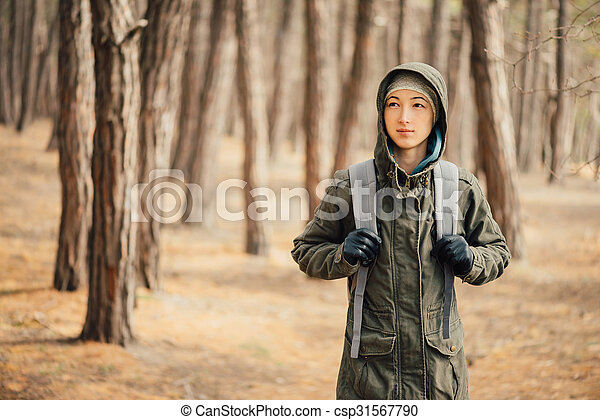 Hiker young woman with backpack walking in the pine forest - csp31567790