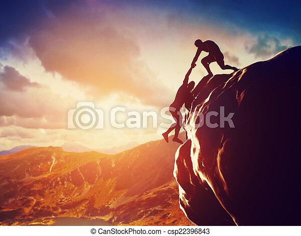 Hikers climbing on rock, mountain  - csp22396843
