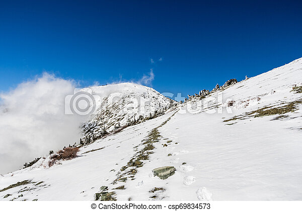 Hiking to the top of Mount San Antonio (Mt Baldy) on a sunny spring day, with frozen snow covering the trail, Los Angeles county, south California - csp69834573