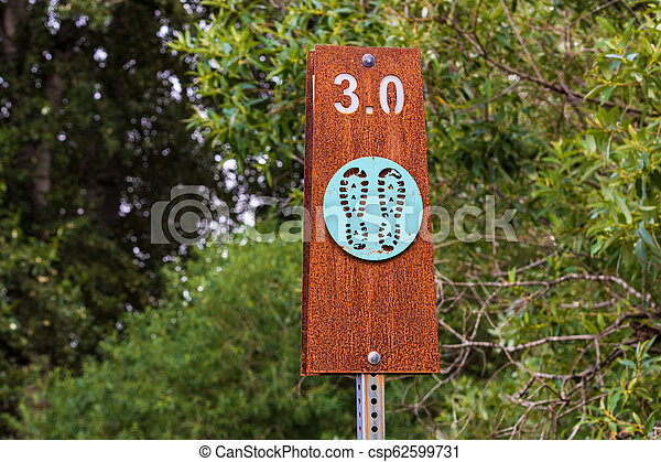 Hiking trail sign post with trees - csp62599731