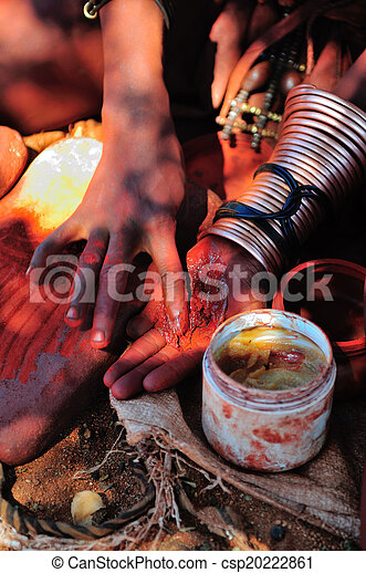 Himba woman mixing red ochre with petroleum jelly - csp20222861