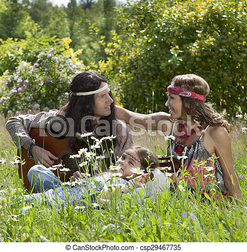 Hippie family playing guitar in the field - csp29467735