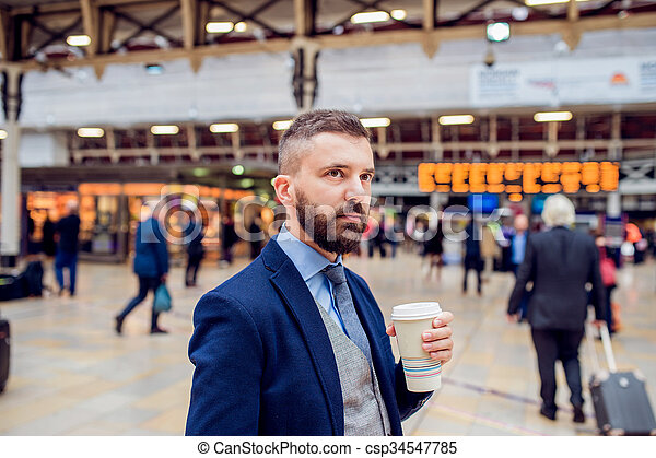 Hipster businessman with coffee cup at the train station - csp34547785