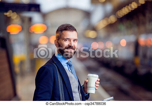 Hipster businessman with coffee cup at the train station - csp34788036