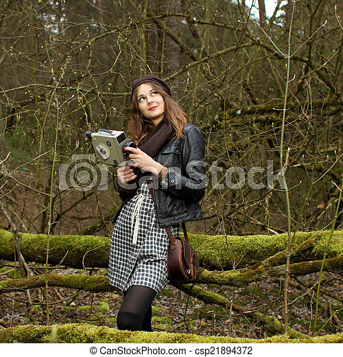 Charming Hipster Girl Is Shooting A Film In The Woods On A Vintage Movie Camera    Csp21894372