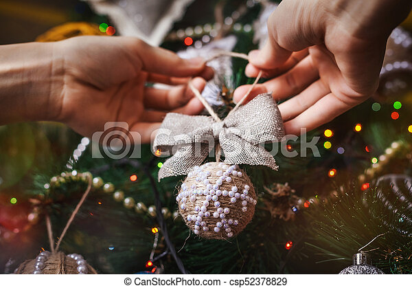 hipster hands with christmas ball and bow and tree background xmas