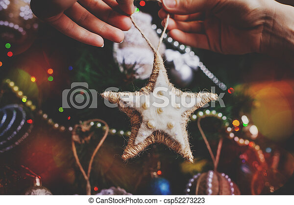 hipster hands with christmas sackcloth star and tree background