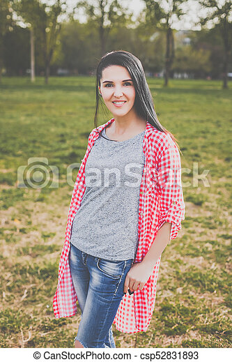 9680e31e0be35f hipster woman in red shirt and ripped jeans posing in park - csp52831893