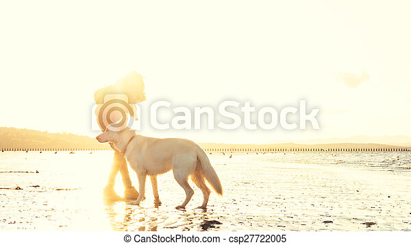 Hipster woman playing with dog at a beach during sunset, strong lens flare effect - csp27722005