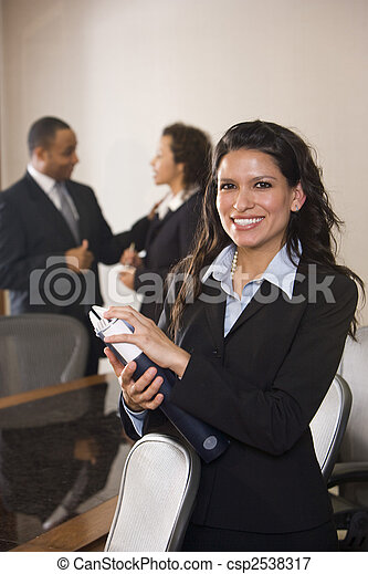 Hispanic businesswoman standing in boardroom, colleagues in background - csp2538317