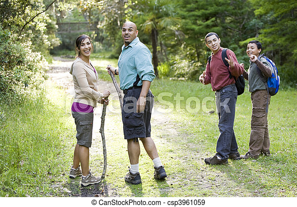 Hispanic family hiking in woods on trail - csp3961059