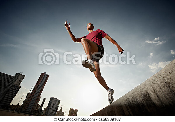hispanic man running and jumping from a wall - csp6309187
