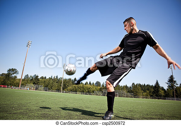 Hispanic soccer or football player kicking a ball - csp2500972