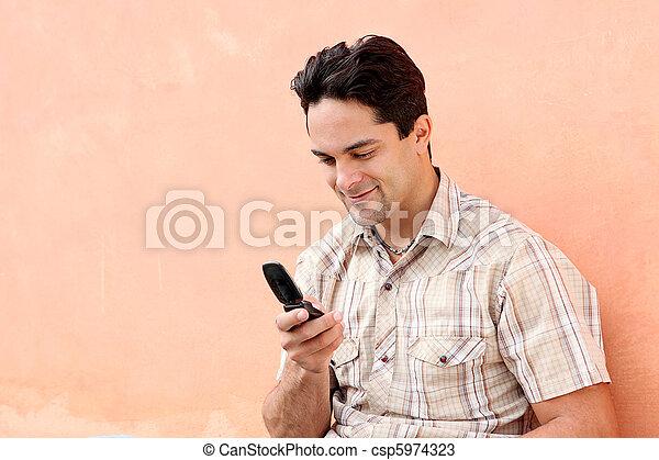 Feliz hombre hispano con celular o móvil - csp5974323
