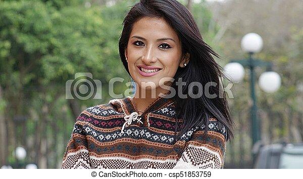 Mujer hispana sonriente en el parque - csp51853759