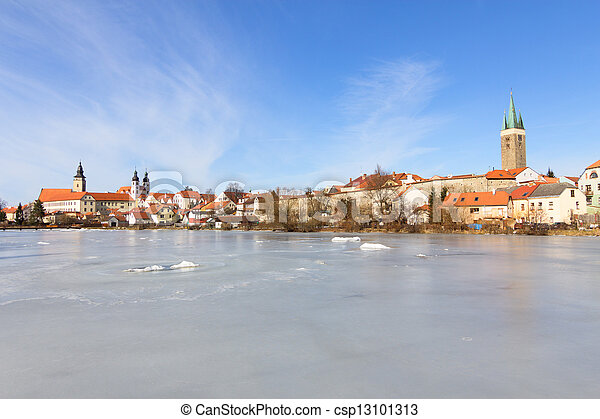 Historic city of Telc in winter with a frozen pond in the foreground - csp13101313