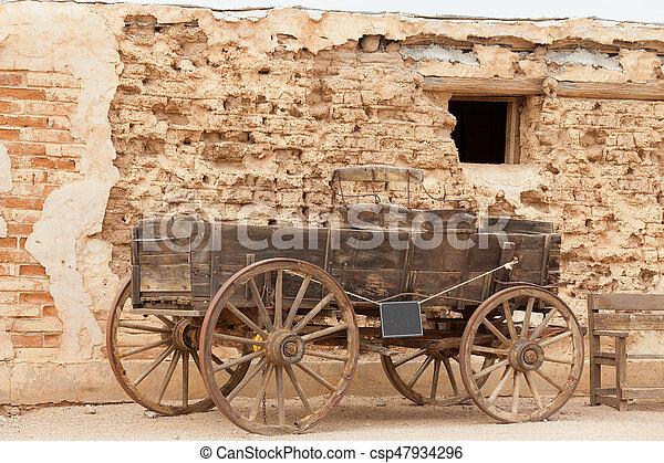 Historic western horse cart dusty mud brick wall - csp47934296