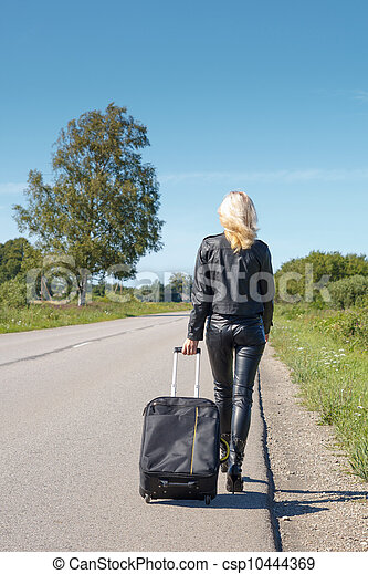 Hitchhiker walking along a rural road - csp10444369