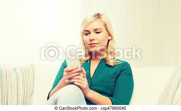 Mujer feliz con teléfono inteligente en casa - csp47660040