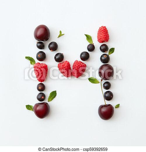 Patrón colorido del alfabeto inglés M de bayas maduras naturales, grosellas, frambuesas, hoja de menta aislada en un fondo blanco. - csp59392659