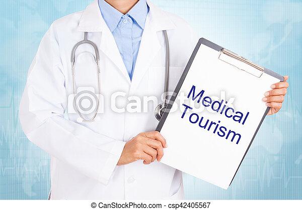 Doctor sosteniendo portapapeles con textos de turismo médico en una hoja de papel. Sobre fondo blanco - csp42405567
