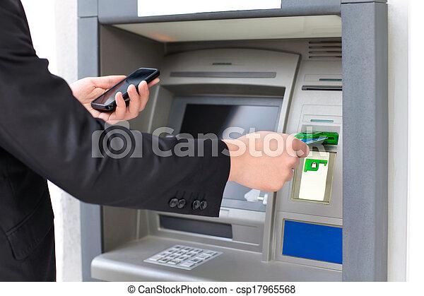 El empresario inserta una tarjeta de crédito en el cajero para retirar dinero y sostener un teléfono - csp17965568