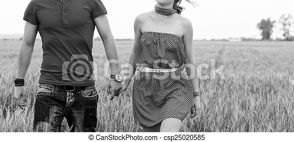 Holding hands couple on green field black and white - csp25020585