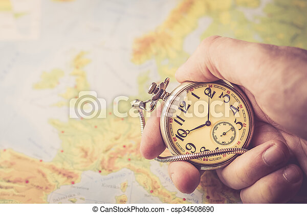 Holding old pocket watch in hand with map of Europe behind
