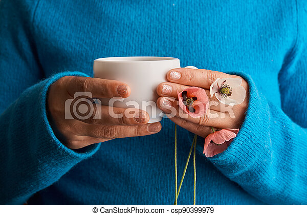 holding poppy flowers and a White cup of warm morning coffee. Blue background. - csp90399979