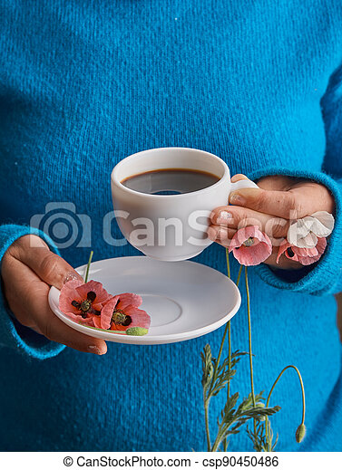 holding poppy flowers and a White cup of warm morning coffee. Blue background. - csp90450486