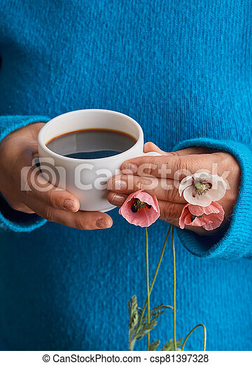 holding poppy flowers and a White cup of warm morning coffee. Blue background. - csp81397328