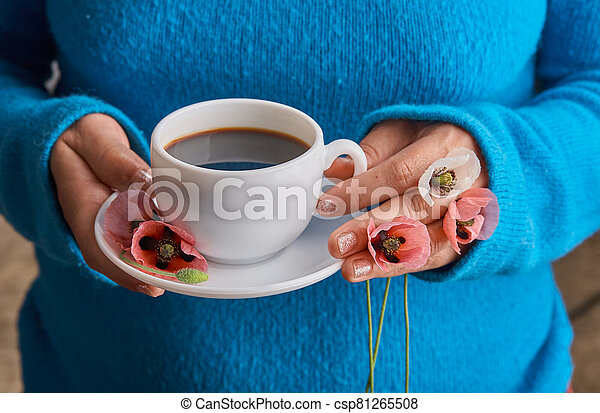 holding poppy flowers and a White cup of warm morning coffee. Blue background. - csp81265508