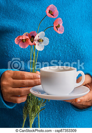 holding poppy flowers and a White cup of warm morning coffee. Blue background. - csp87353309