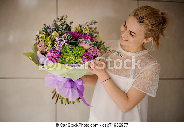 holds bouquet of asters and lilac - csp71982977