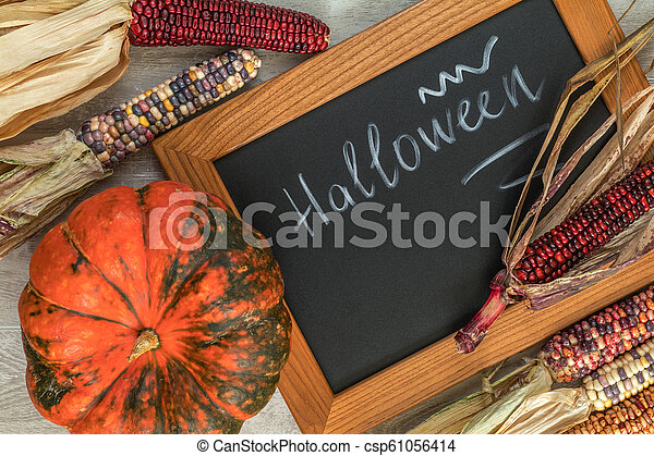 Holiday Halloween background with indian multicolored corn, pumpkin and slate blackboard - csp61056414