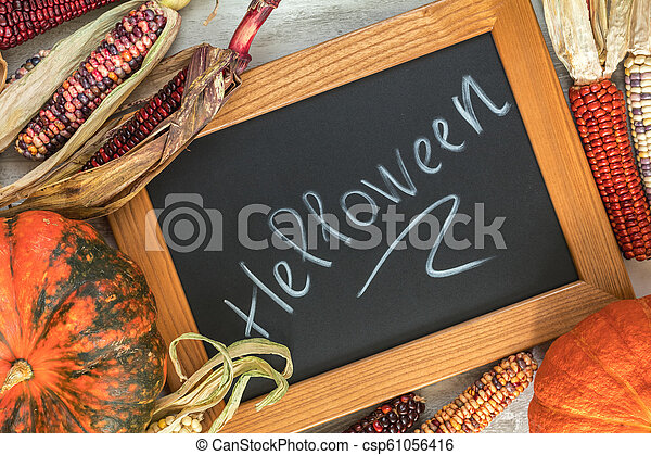 Holiday Halloween background with indian multicolored corn, pumpkin and slate blackboard - csp61056416