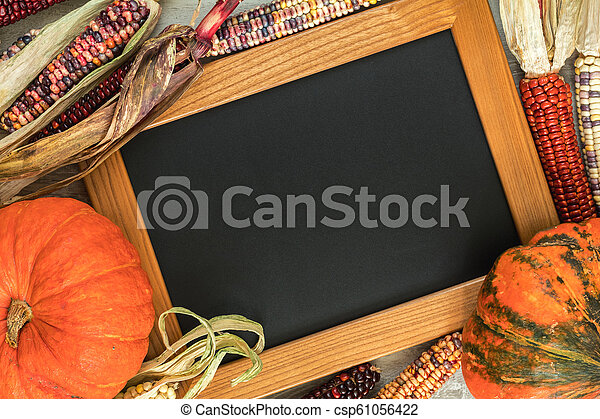 Holiday Halloween background with indian multicolored corn, pumpkin and slate blackboard - csp61056422