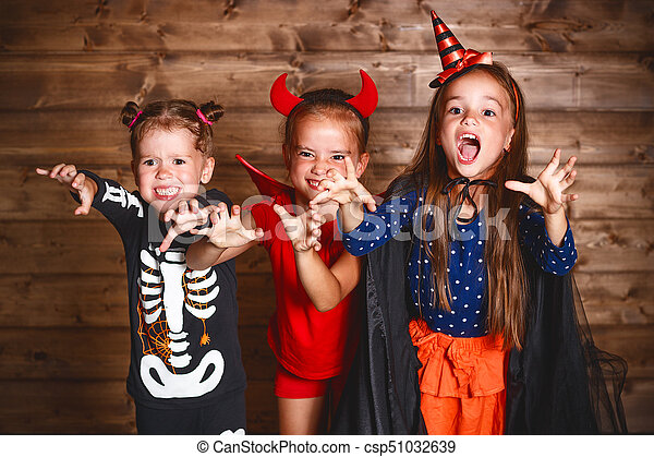holiday halloween. Funny group children in carnival costumes on a wooden background