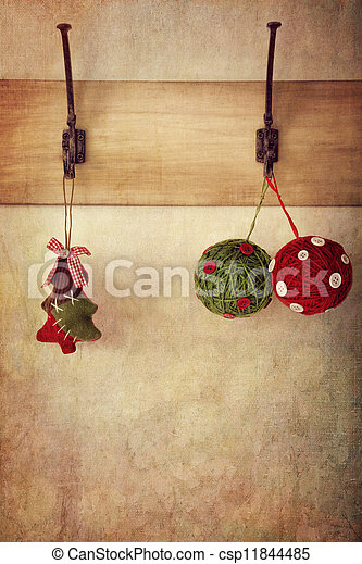 Holiday ornaments hanging on antique wall hooks - csp11844485