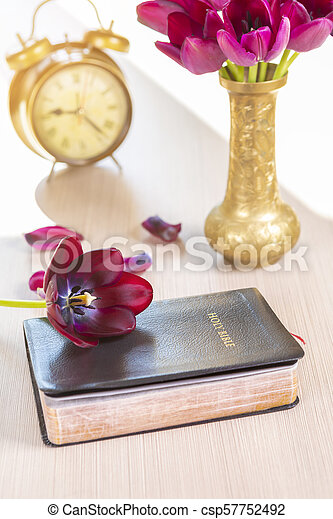 Holy Bible with flowers on wooden table - csp57752492