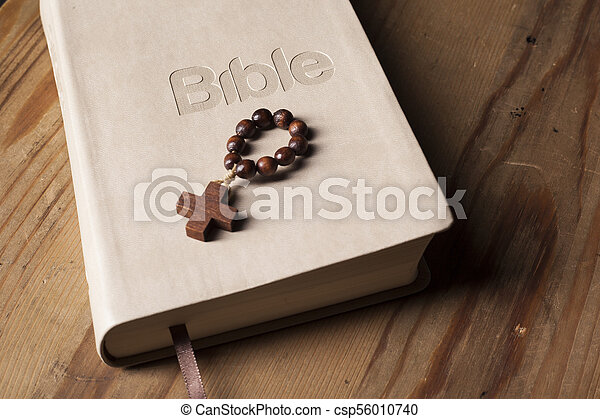 Holy Bible with rosary on wooden table - csp56010740