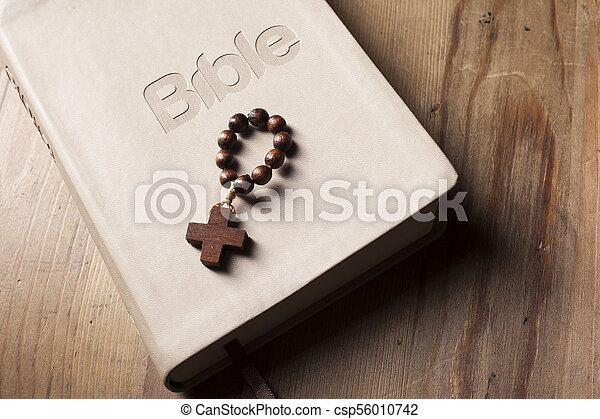 Holy Bible with rosary on wooden table - csp56010742