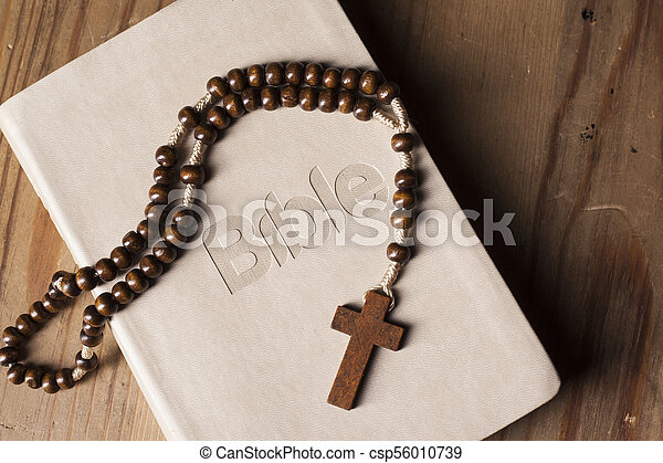 Holy Bible with rosary on wooden table - csp56010739