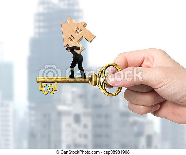Ein Mann mit Holzhaus, der auf dem Schatzschlüssel balanciert - csp38981908