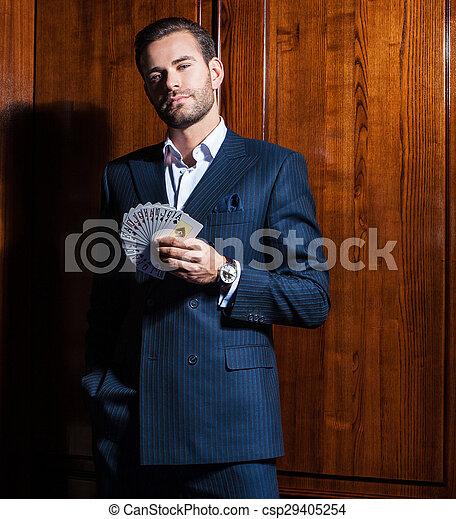 Un hombre guapo con traje posa con tarjetas en el fondo de madera - csp29405254