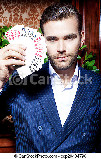 Un hombre guapo con traje posa con tarjetas en el fondo de madera - csp29404790