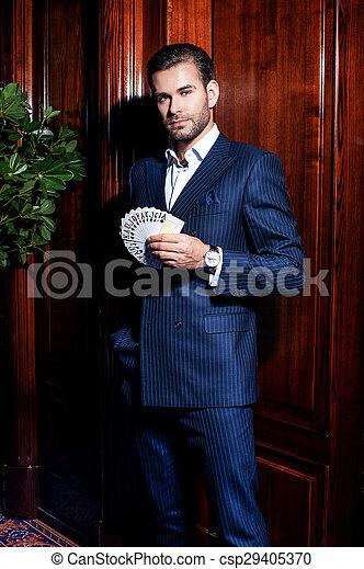 Un hombre guapo con traje posa con tarjetas en el fondo de madera - csp29405370